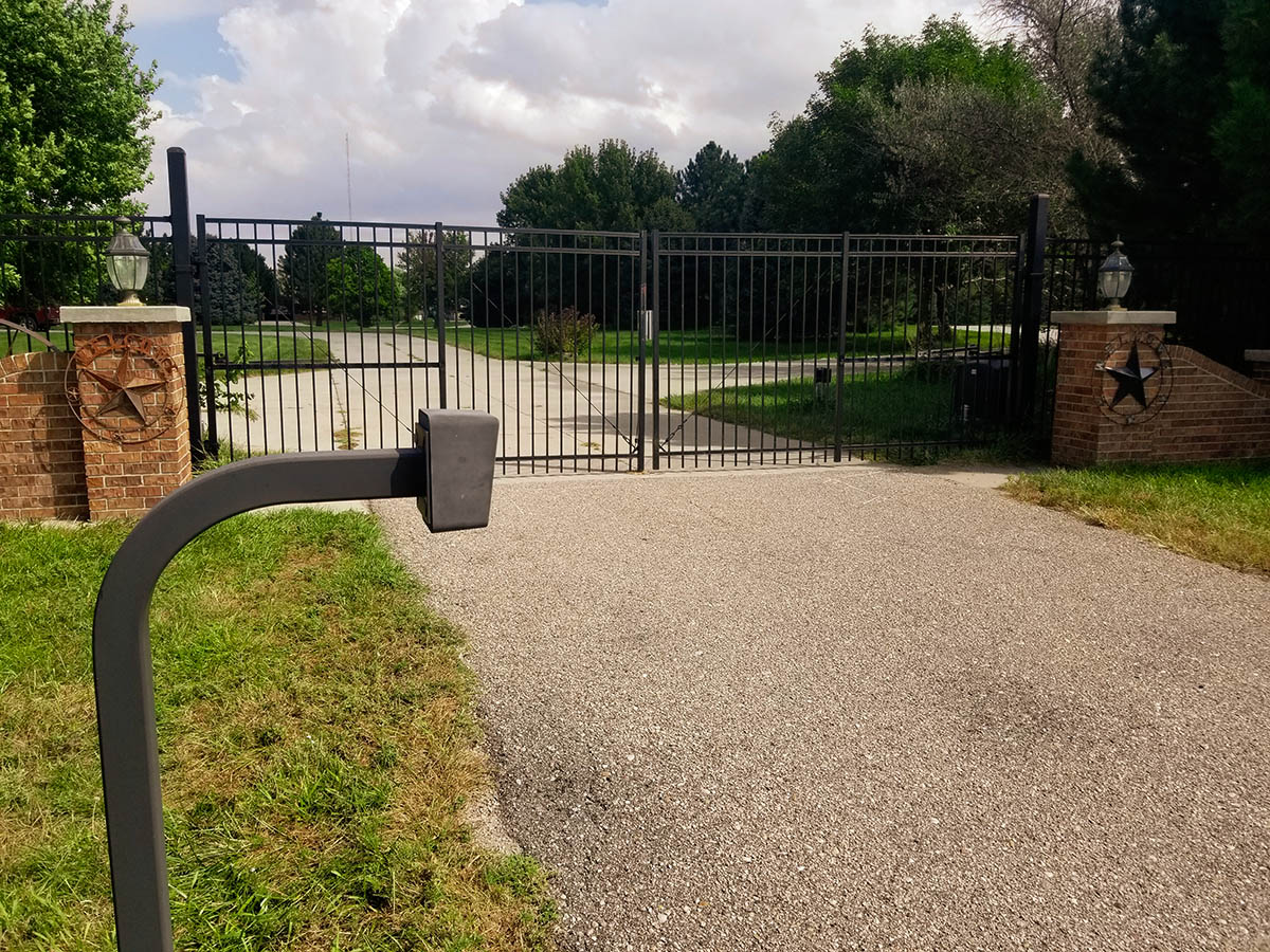 Black ornamental picket style double swing gate with access control pad. Grand Island fence company fence contractors Nebraska gates automation residential commercial